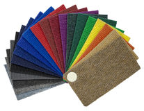 Multi-colored carpeting samples by a fan Stock Images