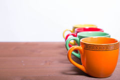Multi-colored ceramic cups stand on the edge of a wooden table stock photo