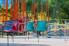 Multi colored chain carousel chairs at noon. Multi colored chain carousel chairs  in amusement park at noon Royalty Free Stock Photo