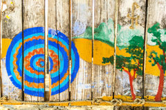 Multi-colored children`s drawing on a wooden fence. Stock Photos