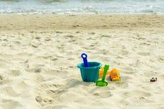 Multi-colored children' s speelgoed in het zand door het overzees royalty-vrije stock foto's