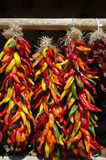 Multi colored chili ristras. Red, yellow green and orange chilies hanging in ristras in open air market Stock Image
