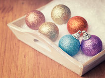 Multi colored christmas ball decorations in white snow Royalty Free Stock Images