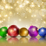 Multi-colored Christmas balls on a gold background Stock Images