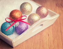Multi colored christmas balls with ribbon decoration in white snow Stock Photo