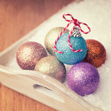 Multi colored christmas balls  in white snow in a tray Royalty Free Stock Images