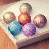 Multi colored christmas decorations in white snow Stock Images