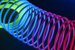 Multi-colored circular objects are lit with fluorescent colors against a deep blue background.