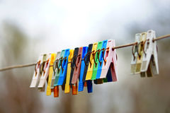 Multi-colored clothes pegs on the rope. Background Stock Images