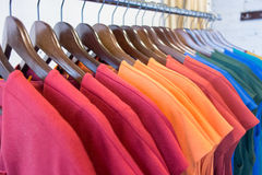 Multi colored clothes on wooden hangers in store. Sale Royalty Free Stock Photos