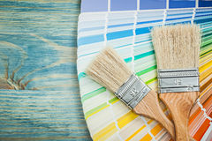 Multi colored color sampler paint brushes on wooden board constr Royalty Free Stock Images