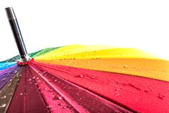 Multi-colored colorful umbrella with all colors of the rainbow with raindrops isolated royalty free stock photography