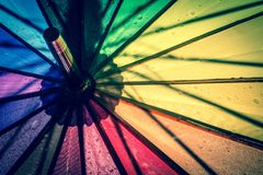 Multi-colored colorful umbrella with all colors of the rainbow with raindrops. Vintage, grunge, retro style photo. stock photos