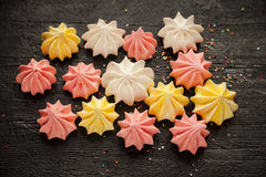 Multi-colored confetti and meringue. Meringues and confetti lying on a black wooden background Stock Image
