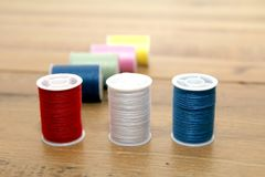 Multi-colored cotton reels or bobbins on a wooden needlework tab. Le Royalty Free Stock Image