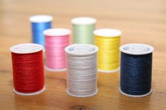 Multi-colored cotton reels or bobbins on a wooden sewing table.  Royalty Free Stock Photo