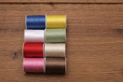 Multi-colored cotton reels or bobbins on a wooden sewing table.  Royalty Free Stock Images