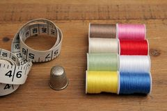 Multi-colored cotton reels, tape measure and thimble on a wooden. Sewing table Stock Photos