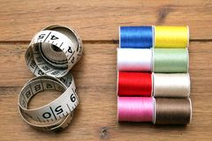 Multi-colored cotton reels and tape measure on a wooden sewing t. Able Royalty Free Stock Image