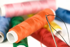 Multi colored cotton with threaded needle Royalty Free Stock Image