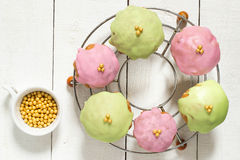 Multi-colored cupcakes on a wire rack and sugar beads Royalty Free Stock Photography