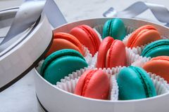 Multi-colored delicious homemade macarons in a round white box on a marble background stock photo