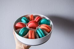 Multi-colored delicious homemade macarons in a round white box on a marble background royalty free stock photos