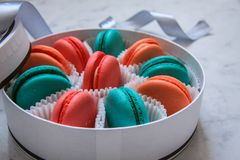Multi-colored delicious homemade macarons in a round white box on a marble background stock image