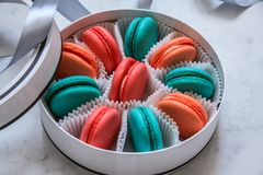 Multi-colored delicious homemade macarons in a round white box on a marble background royalty free stock image
