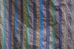 A multi-colored dense canvas wrinkled fabric with vertical lines. rough surface texture stock photography