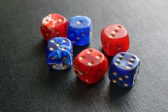 Dice lying on a black textured surface. Multi-colored dice lying on a black textured surface Royalty Free Stock Photography