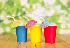 Multi-colored Disposable Paper Cups And Straws On Abstract Green. Royalty Free Stock Image