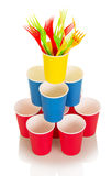 Multi-colored disposable paper cups and colorful plastic forks isolated. Stock Photo