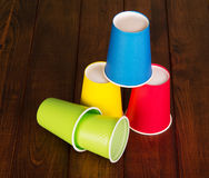 Multi-colored disposable paper, plastic cups on background dark wood. Royalty Free Stock Photos