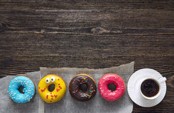 Multi-colored donuts with a cup of coffee on a wooden table. Cop Stock Images