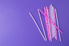 Multi Colored drinking straws on purple background stock image