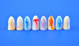 Multi-colored earplugs stand in row on a blue background. Multi-colored earplugs stand in a row on a blue background stock images