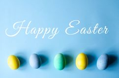 Multi-colored Easter eggs on a blue background stock images
