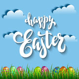 Multi colored easter eggs in grass against the blue sky and clou. Ds with the handwriting lettering Happy Easter Royalty Free Stock Photos