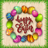 Multi colored easter eggs and grass on a wood background with th. E hand drawn lettering Happy Easter Royalty Free Stock Photos