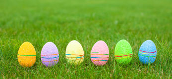 Multi-colored Easter eggs on green grass Stock Images