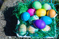 Multi colored Easter eggs in green plastic grass stock images