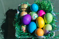 Multi colored Easter eggs in green plastic grass stock photos