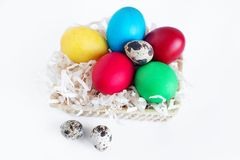 Multi-colored Easter eggs lie in a basket on a white background. Yellow, red, green and quail eggs in a basket stock photo