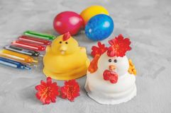 Multi-colored Easter eggs lie next to paint for coloring and marzipan Easter cakes in the shape of chickens royalty free stock photos