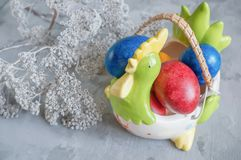 Multi-colored Easter eggs lie on a white plate in the shape of a chicken next to paint for coloring and Easter cakes stock image