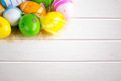 Multi colored Easter eggs on  white wooden board background Stock Image