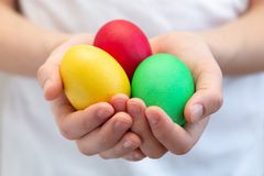 Multi-colored eggs in children`s hands. Yellow, red, green eggs in the hands of a boy royalty free stock images