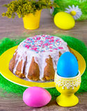 Multi-colored eggs and Easter cake on a yellow plate Royalty Free Stock Images