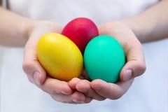 Multi-colored eieren in de handen van kinderen Gele, rode, groene eieren in de handen van een jongen stock fotografie